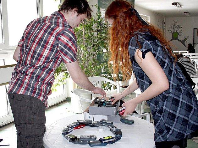 Studenti srovnávají vysloužilé telefonní přístroje, které prozatím vybrali k recyklaci. Další sbírají.