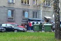 Někteří lidé čekají na zbytky, které zaměstnanci obchodu vyhodí do kontejnerů