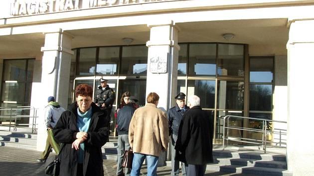 Magistrát byl evakuován. Primátor (vpravo) se dotazuje policisty, kdy bude prohlídka budovy ukončena.