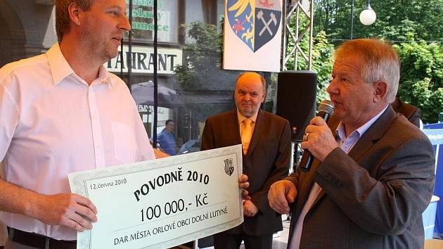 Starosta Dolní Lutyně Pavel Buzek (vlevo) přebírá z rukou orlovského kolegy Jiřího Michalíka šek na 100 tisíc korun.