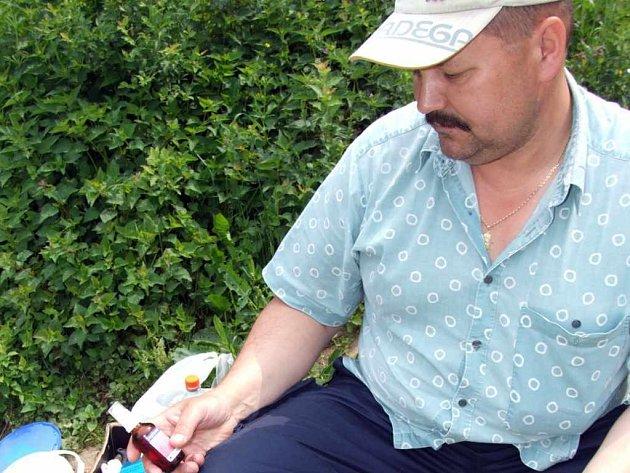Rybář ukazuje lahvičku s desinfekcí, kterou ulovené ryby pravidelně ošetřuje.