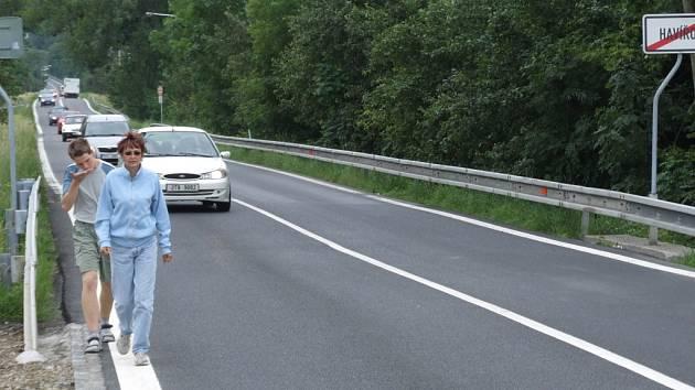 Žena se synem jdou po frekventované silnici, kde není chodník
