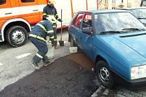 Hasiči likvidují benzin vyteklý na silnici