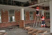 Dělníci rozebírají vnitřek budovy, v níž byla asijská tržnice. Objekt bude stržen a na jeho místě bude stát parkoviště.