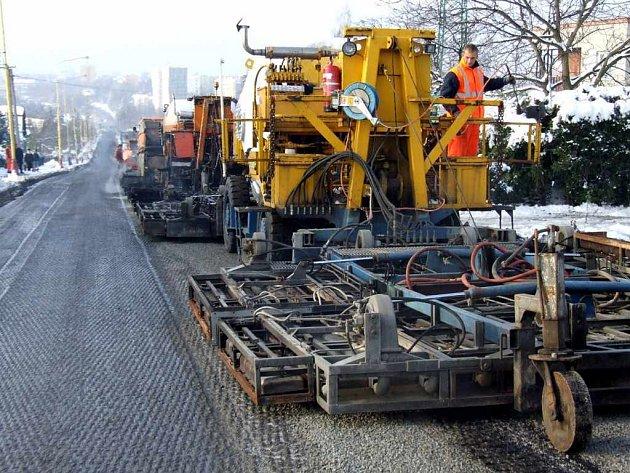 Sestava strojů sloužících k horkému pokládání asfaltového koberce byla o víkendu i v pondělí v nepřetržitém pohybu od rána do večera.