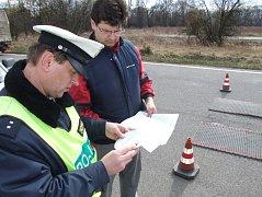 Dopravní policista čte záznam z papírových koleček z tachografu.