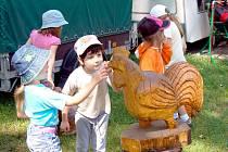 Děti si prohlížejí jednu z dřevěných plastik