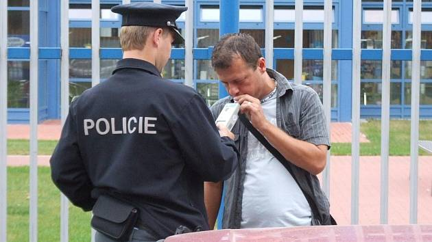 Policista nechává u opilého řidiče provést dechovou zkoušku. Ilustrační foto