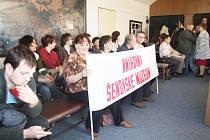 Lidé s transparentem na zasedání městského zastupitelstva
