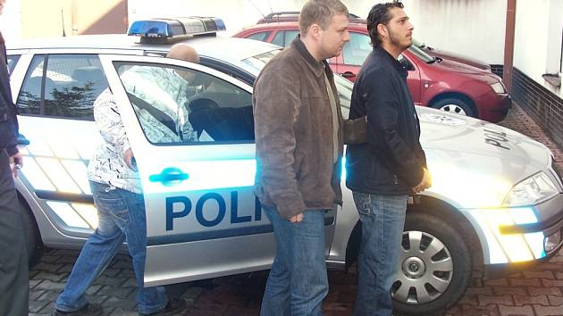 Policista předvádí k výslechu jednoho ze zadržených mužů, kteří se vyhýbali nástupu do věznice.