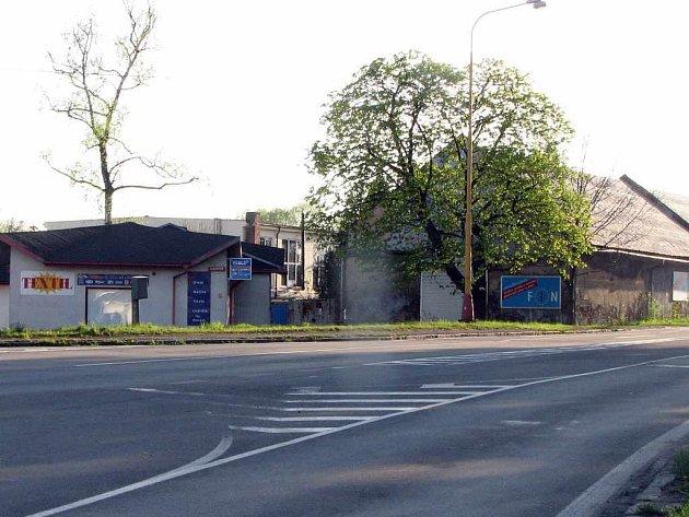 Současnost. V místech, kde stál zámek, se nachází části křižovatky a nákupní centrum. V pozadí je bývalá hospodářská budova.
