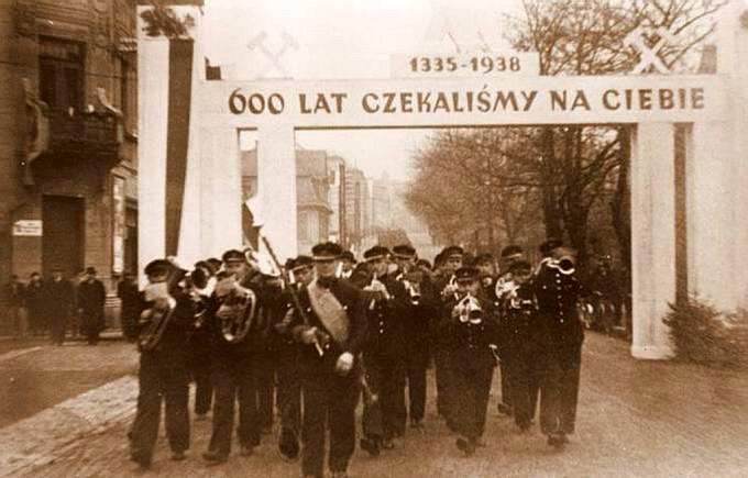 """Další útok. Polská vojenská kapela vstupuje v roce 1938 do Karviné pod nápisem """"600 let jsme na tebe čekali"""", připraveným místními Poláky"""