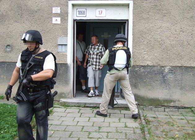 Pro hledaného si přišli ozbrojení policisté. Zadržený je v doprovodu eskorty ještě uvnitř domu.