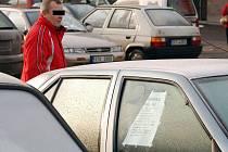 Muž prochází kolem aut nabízených k prodeji.