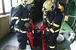Figuranta hasiči uložili do nosítek a snesli ho po schodech dolů.