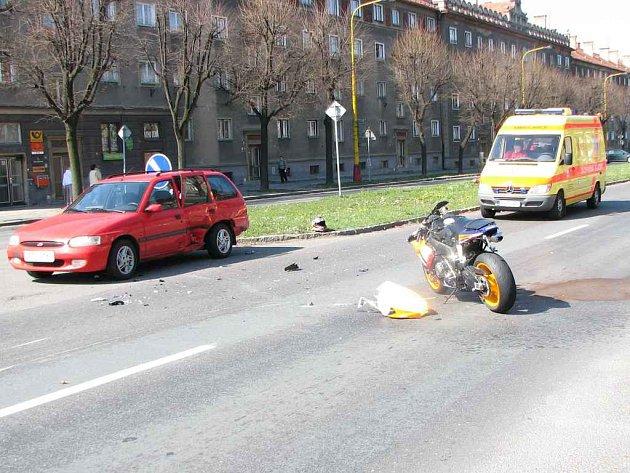 Fotografie zachycuje situaci krátce po nehodě. Zbytečnou smrt motorkáře připomíná křížek a hořící svíčky.