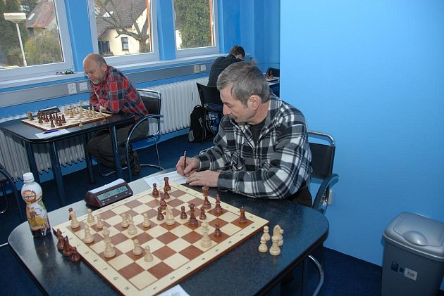 Vpravo v kárované košili je karvinský hráč Josef Lys, který v Brně vyhrál nad Karlem Dvořákem a přispěl k bodu Šachového klubu.