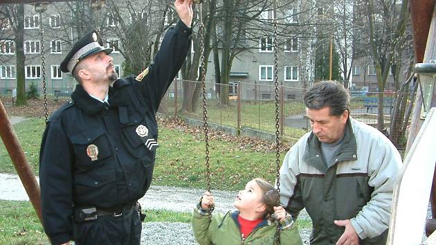 Strážník zjišťuje stav poškozené houpačky.