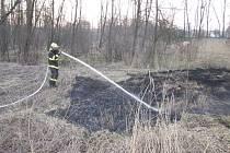 Hasič prolévá vodou místo, kde hořela suchá tráva.