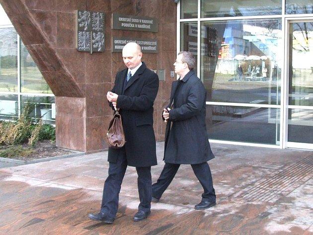 Lékař Jan Noga (vpravo) odchází z justiční budovy.