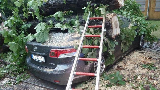 Během průtrže mračen spadl po zásahu blesku vzrostlý strom na zaparkované vozidlo Toyota Avensis v nemocničním areálu.