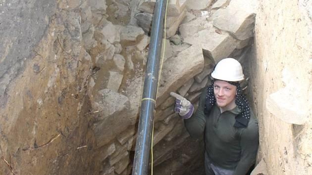 Jeden z archeologů provádějících výzkum ukazuje část zaniklé opavské hradby, tzv. parkánové zdi, ležící v sousedství křižovatky ulice Praskova a Nádražního okruhu. Ilustrační foto.
