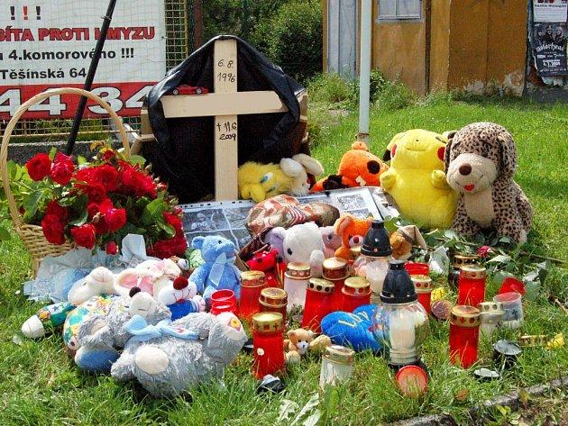 Kříž, přes něho přehozená chlapcova bunda, plyšáci, hračky, rybářský prut, svíčky. Tak vypadá pomníček v místě tragické smrti dvanáctiletého chlapce v Opavě – Komárově.