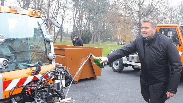 Starosta Andreas Hahn křtí šampaňským nový samosběrný vůz učený k snižování prašnosti v Kravařích.