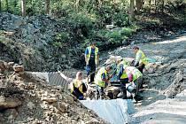 Dělníci pracují v korytu řeky u Zálužného. Na mostě, který je nad nimi, je omezena doprava.