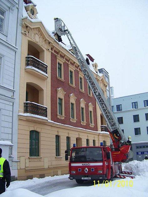 S odstraňováním nebezpečného sněhu na vysokých domech v centru Hlučína pomáhali hasiči z místní základny.