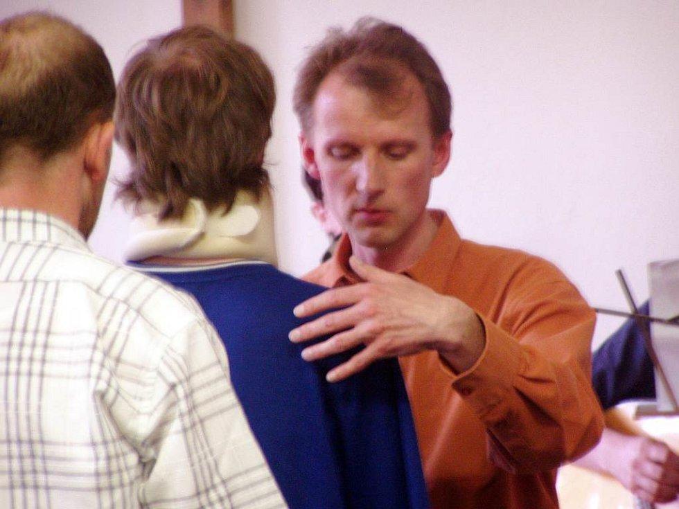 Přednášející při uzdravování muže, který měl údajně problémy s hybností ruky.