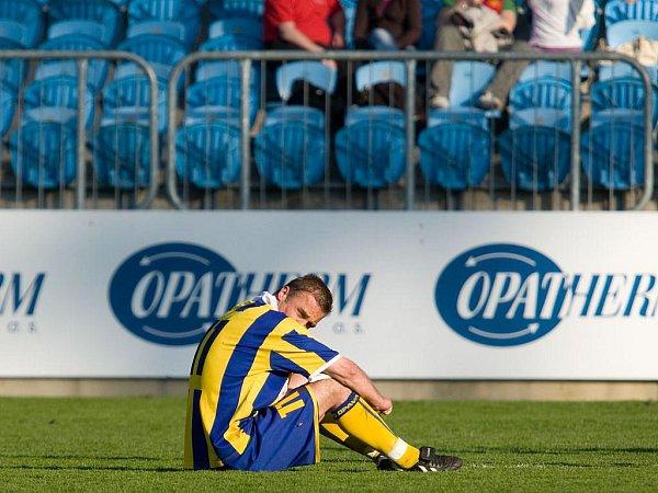 Zhrzený kapitán SFC Opava Jaroslav Kolínek. Po prohraném utkání sJihlavou seděl zničený na trávníku. Opava prohrála a dál se nachází vtěsné blízkosti sestupových vod, on navíc vtřetí minutě nastavení nedal penaltu, která by znamenala alespoň bod.