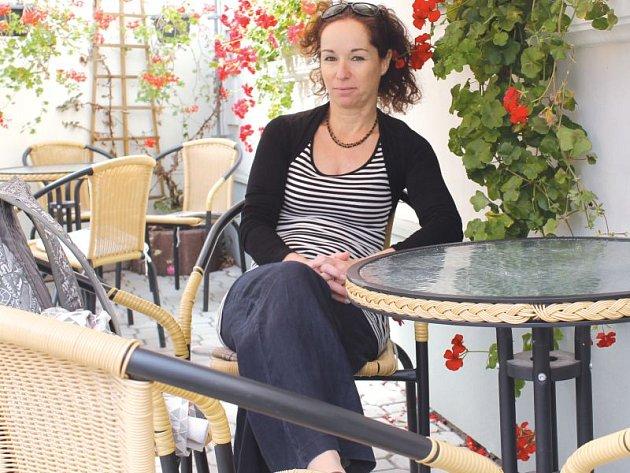 """Hana Fischerová čeká na zahrádce cukrárny Posezení u pekaře na kávu a zákusek. Ve čtvrtek krátce po polední byla jednou z mála, kteří seděli venku. """"Musím na čerstvý vzduch. Právě mám za sebou státnice na Institutu tvůrčí fotografie,"""" řekla."""