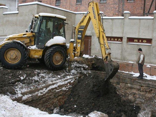 Bagr se na počátku prosince roku 2010 chystá na zakousnutí do nedokončených archeologických vykopávek za domem U Mouřenína.