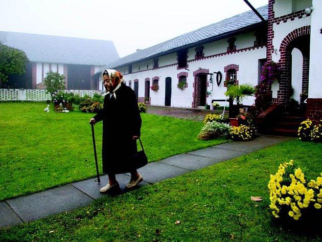 Cesta do kostela. Babička jde na nedělní mši. Ze snímku můžeme cítit tradici.