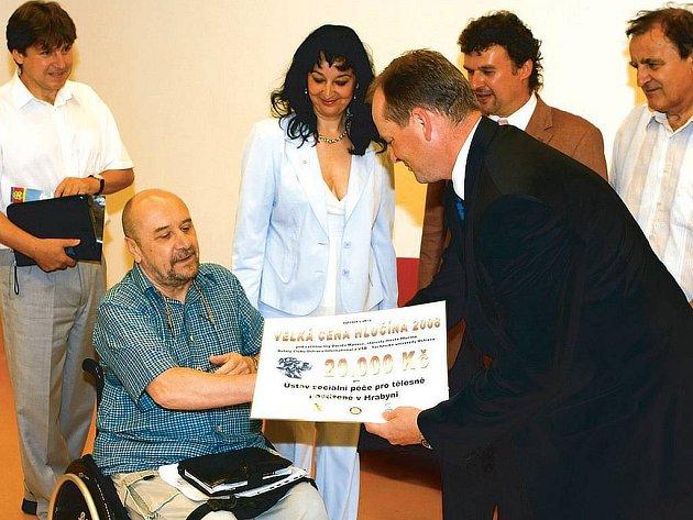 Starosta Hlučína David Maňas předává v Hrabyni šek, který má pomoci postiženým sportovcům.