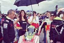 Michaela Dihlová na Velké ceně Brna drží deštník italskému závodníkovi Andreu Iannonemu.