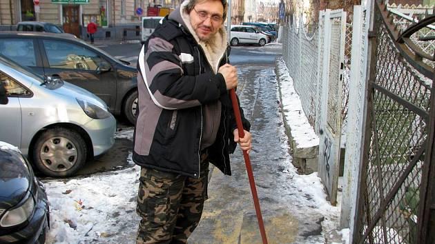 Petr Dehner odklízí zledovatělý sníh před svým domem v Opavě.