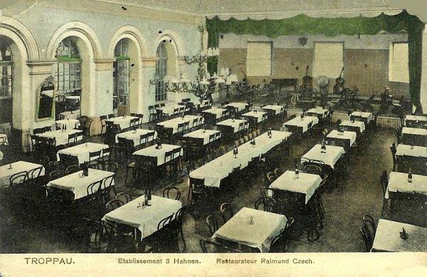 Na dobovém snímku je zachycen hlavní sál restaurace Utří kohoutů.