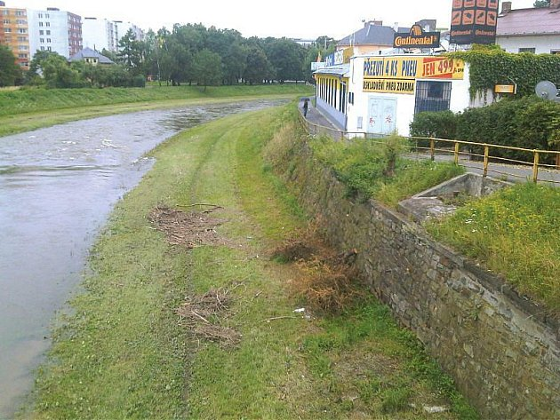Břehy řeky Opavy jsou po deštích zaneseny nepořádkem. Fotografie byla pořízena v pondělí dopoledne z mostu na Pekařské ulici.