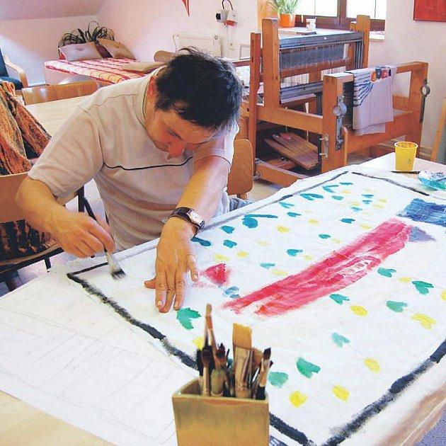 Jarek Vltavský z charitní dílny Radost maluje jeden z obrazů určených pro výstavu.