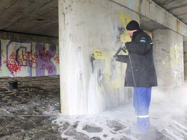 Jeden ze zaměstnanců firmy Nanoteam pracuje na odstranění graffiti pod mostem na Ratibořské ulici v Opavě.