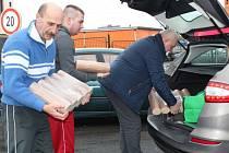 Pavel Paschek předává dřevěné brikety rodině Sedláčkových.