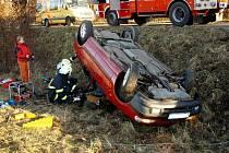 Záchrana řidiče. Hasiči vyprošťují řidiče, jehož hlava zůstala po havárce u Hrabyně zaklíněna v jeho poničeném voze.