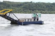 Vodní kombajn seče v Hlučínském jezeře vodní traviny, které brání v pohybu plavcům, ale třeba také záchranářským člunům.