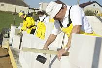 Stavbaři při práci na unikátním projektu, jímž je zbudování hrubé stavby rodinného domu během pouhých 24 hodin.