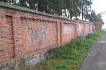 Graffiti na hřbitovní zdi.