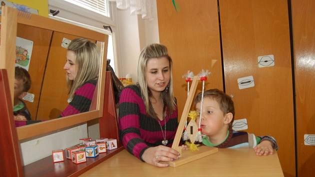 Malý Péťa pod vedením své paní učitelky fouká do dráčka, aby se naučil správně dýchat.