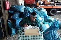 Zaměstnanec budišovských technických služeb váží modré pytle s vytříděným papírem.