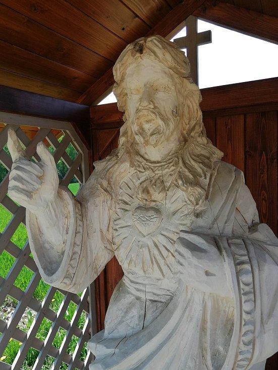 Dřevěná socha Ježíše hlídá obec na konci nové cyklostezky.